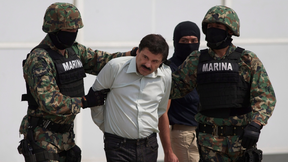 "In this Saturday, Feb. 22, 2014 file photo, Joaquin ""El Chapo"" Guzman, centre, is escorted to a helicopter in handcuffs by Mexican navy marines at a hanger in Mexico City, after he was captured overnight in the beach resort town of Mazatlan. (AP Photo/Eduardo Verdugo)"