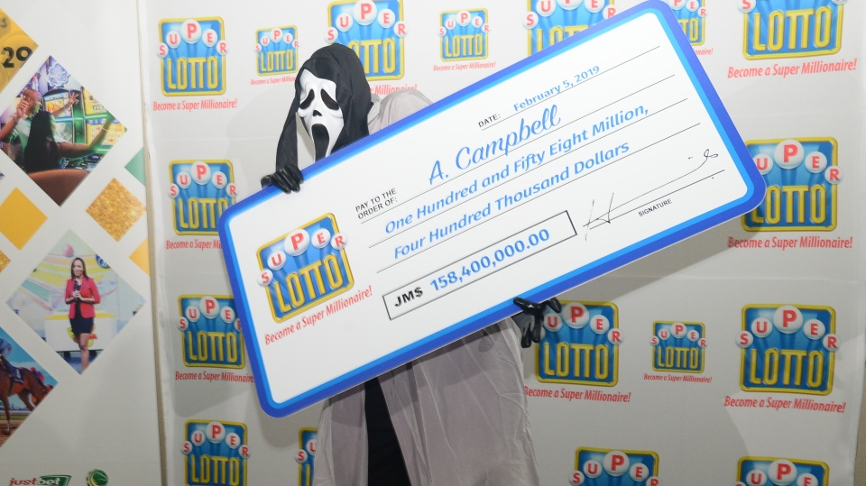 Super Lotto winner A. Campbell poses with a novelty cheque in Kingston, Jamaica on Feb. 5, 2019. (Courtesy: Supreme Ventures)