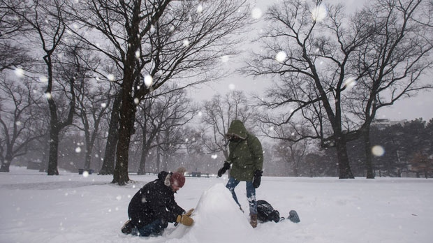 Rafael Ravara, left, and Alano Silva, take advantage of the winter storm to build their first snowman at High Park in Toronto on Tuesday, February 12, 2019. (THE CANADIAN PRESS/ Tijana Martin)