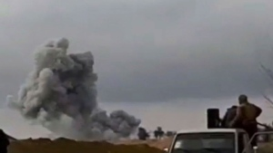 This frame grab from video provided on Tuesday, Feb. 12, 2019, by the Syrian Observatory for Human Rights, an opposition group, that is consistent with independent AP reporting, shows U.S.-backed Syrian Democratic Forces fighters looking at smoke rising from a shell that targeted Islamic State group militants, in the village of Baghouz, Deir El-Zour, eastern Syria. (Syrian Observatory for Human Rights via AP)