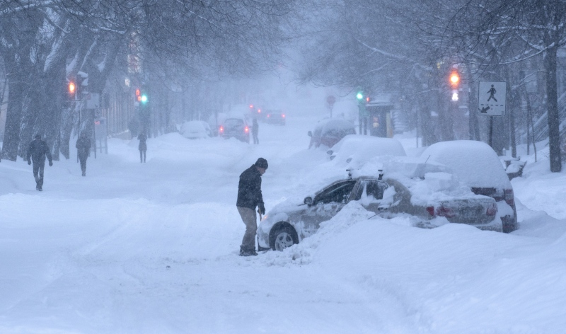 A man tries to get his car out that is stuck in a snowbank during a winter storm in Montreal on Wednesday, Feb. 13, 2019. THE CANADIAN PRESS/Paul Chiasson
