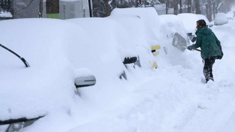 A woman digs her car out of a snowbank during a winter storm in Montreal on Wednesday, February 13, 2019. THE CANADIAN PRESS/Paul Chiasson