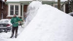 James Liston throws snow onto a massive snow pile as he helps clear snow from a neighbour's driveway in Ottawa's Glebe neighbourhood during a winter storm on Wednesday, Feb. 13, 2019. THE CANADIAN PRESS/Justin Tang