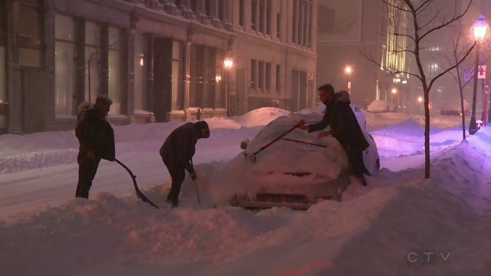 Three men teamed up to clear snow off a car and to shovel it out of a snowdrift on Feb. 13, 2019