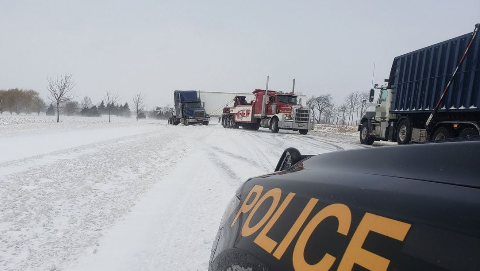 A tow truck works to remove a tractor trailer on Highway 24 after a crash north of Simcoe, Ont. on Wednesday, Feb. 13, 2019. (@OPP_WR / Twitter)