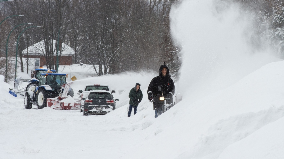 Residents clean up Wednesday, February 13, 2019 in Deux-Montagnes, Que, after a storm dumped almost 40 centimetres of snow in the Montreal area. THE CANADIAN PRESS/Ryan Remiorz