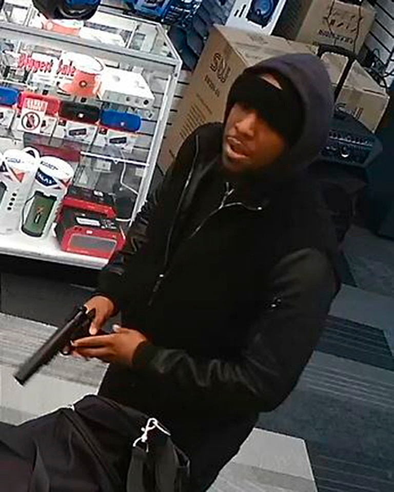 In this image taken from surveillance video provided by the New York Police Department, a man, identified by police as Christopher Ransom, is shown robbing a cell phone store, Saturday, Jan. 19, 2019 in the Queens borough of New York. Police say that Ransom is also a suspect in the robbery of another cell phone store in Queens that led to the fatal shooting of a detective on Tuesday, Feb. 12, 2019. (AP Photo/NYPD)