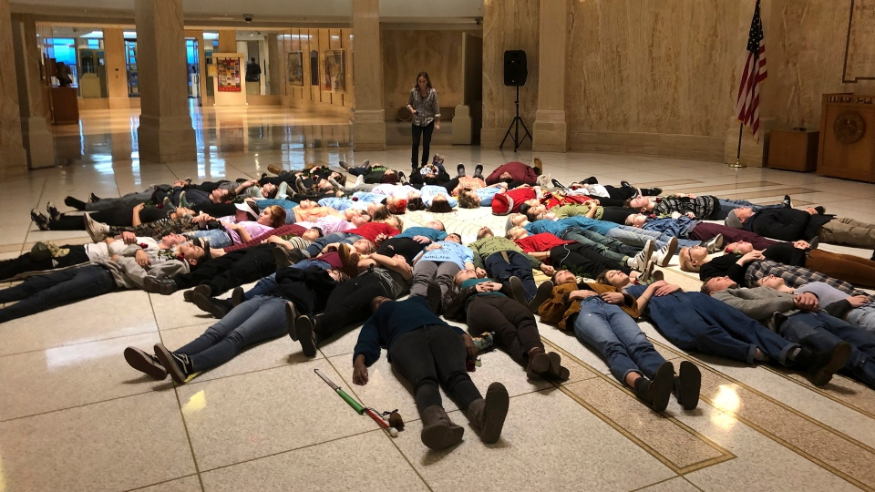 Student advocates for new gun safety regulations hold a silent 'lie-in' protest in the state Capitol in Santa Fe, N.M., on Wednesday, Feb. 13, 2019, in anticipation of the anniversary Thursday of the mass shooting at Marjory Stoneman Douglas High School in Parkland, Fla. (AP Photo/Morgan Lee)