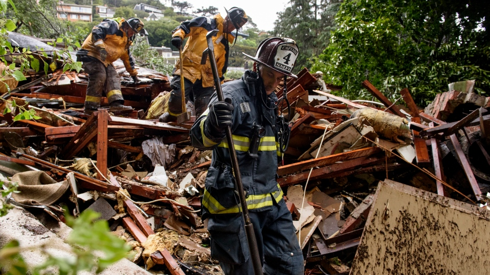 Southern Marin Fire Department members search a crushed house in the aftermath of a mudslide that destroyed three homes on a hillside in Sausalito, Calif., Thursday, Feb. 14, 2019. (AP Photo/Michael Short)