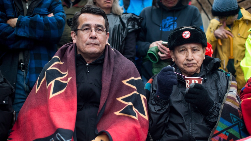 Union of B.C. Indian Chiefs Vice President Chief Bob Chamberlin, left, and Grand Chief Stewart Phillip, President of the Union of B.C. Indian Chiefs, join protesters opposed to the Kinder Morgan Trans Mountain pipeline extension and defy a court order blocking an entrance to the company's property, in Burnaby, B.C., on Saturday April 7, 2018. The pipeline is set to increase the capacity of oil products flowing from Alberta to the B.C. coast to 890,000 barrels from 300,000 barrels. THE CANADIAN PRESS/Darryl Dyck