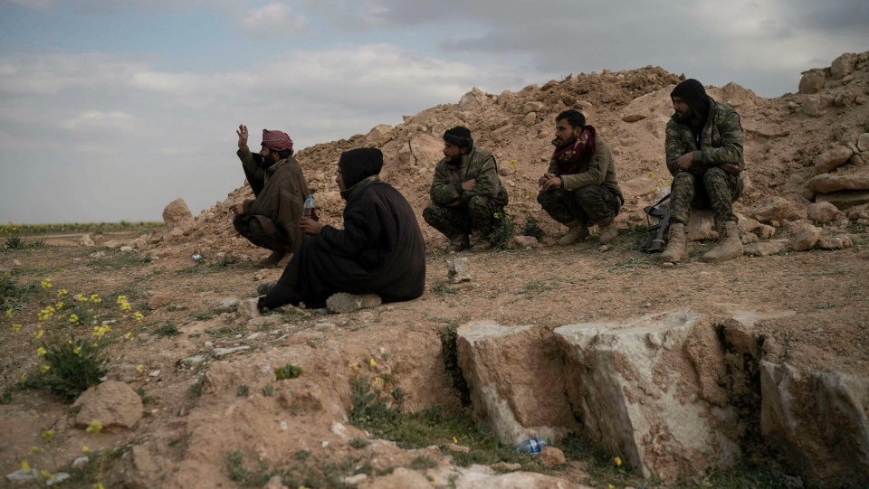 U.S.-backed Syrian Democratic Forces (SDF) fighters sit atop a hill in the desert outside the village of Baghouz, Syria, Thursday, Feb. 14, 2019. (AP Photo/Felipe Dana)