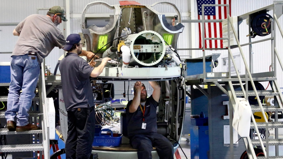 In this May 4, 2018 photo, technicians works on the wiring of a twin-engine Lakota helicopter, at the Airbus Helicopters, Inc., manufacturing facility in Columbus, Miss. (AP Photo/Rogelio V. Solis)