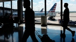 In this Aug. 1, 2016 file photo, passengers walk to their gates through the terminal as American Airlines planes wait to depart at O'Hare International Airport in Chicago. (AP Photo/Kiichiro Sato)