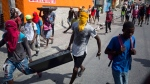 Masked looters carry a flat screen TV amid protests demanding the resignation of Haitian President Jovenel Moise near the presidential palace in Port-au-Prince, Haiti, Wednesday, Feb. 13, 2019. Protesters are angry about skyrocketing inflation and the government's failure to prosecute embezzlement from a multi-billion Venezuelan program that sent discounted oil to Haiti. (AP Photo/Dieu Nalio Chery)