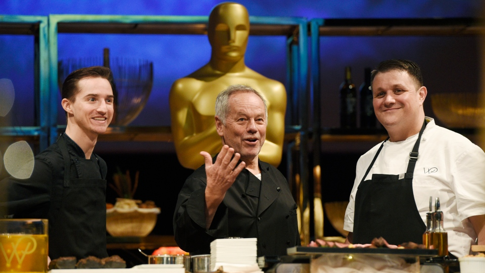 Chef Wolfgang Puck, center, is flanked by his son Byron, left, and Eric Klein, vice president of culinary at Wolfgang Puck Catering, at the press preview for the 91st Academy Awards Governors Ball, Friday, Feb. 15, 2019, in Los Angeles. This year marks the 25th year Wolfgang Puck has catered the Governors Ball, the official afterparty of the Academy Awards. (Photo by Chris Pizzello/Invision/AP)