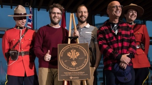 Seth Rogen, second left, Evan Goldberg, centre, and Howie Mandel pose for photographs with Royal Canadian Mounted Police officers after unveiling a Canada's Walk of Fame plaque honouring Rogen and Goldberg during a ceremony, in Vancouver, on Friday February 15, 2019. THE CANADIAN PRESS/Darryl Dyck