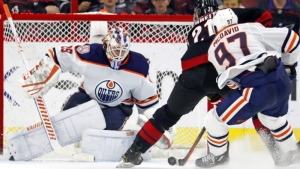 Carolina Hurricanes' Nino Niederreiter (21) makes a move on Edmonton Oilers goaltender Mikko Koskinen (19) with Connor McDavid (97) giving chase during the third period of an NHL hockey game Friday, Feb. 15, 2019, in Raleigh, N.C. (AP Photo/Karl B DeBlaker)