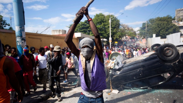 A masked man hits the ground with a stick as protesters demand the resignation of Haitian President Jovenel Moise in Port-au-Prince, Haiti, Tuesday, Feb. 12, 2019. (AP / Dieu Nalio Chery)