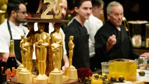 Twenty-four karat gold-dusted Valrhona Illanka Chocolate Oscars stand near chef Wolfgang Puck, far right, and his son Byron as they are interviewed at the press preview for the 91st Academy Awards Governors Ball, Friday, Feb. 15, 2019, in Los Angeles. This marks the 25th year Puck has catered the Governors Ball. The 91st Academy Awards will be held on Sunday, Feb. 24, at the Dolby Theatre in Los Angeles. (Photo by Chris Pizzello/Invision/AP)