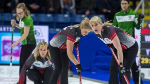 Team Canada skip Jennifer Jones, left, looks on as second Jocelyn Peterman and lead Dawn McEwan, right, sweep a rock as they play Saskatchewan at the Scotties Tournament of Hearts at Centre 200 in Sydney, N.S. on Saturday, Feb. 16, 2019. THE CANADIAN PRESS/Andrew Vaughan