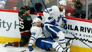 Arizona Coyotes center Nick Cousins (25), Toronto Maple Leafs defenseman Morgan Rielly (44) and Maple Leafs defenseman Jake Muzzin (8) collide during the third period of an NHL hockey game Saturday, Feb. 16, 2019, in Glendale, Ariz. (AP Photo/Ross D. Franklin)