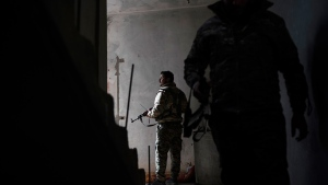 U.S.-backed Syrian Democratic Forces (SDF) fighters walk in a building as fight against Islamic State militants continue in the village of Baghouz, Syria, Saturday, Feb. 16, 2019. (AP Photo/Felipe Dana)