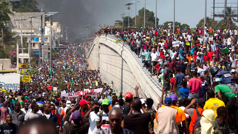 In this Feb. 7, 2019 photo, thousands of demonstrators march in the street as they chant anti-government slogans during a protest to demand the resignation of President Jovenel Moise and demanding to know how Petro Caribe funds have been used by the current and past administrations, in Port-au-Prince, Haiti. (AP Photo/Dieu Nalio Chery)