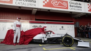 Drivers Kimi Raikkonen of Finland, left, and Antonio Giovinazzi of Italy, center, unveil the new Alfa Romeo F1 car during a presentation of the new livery at the Barcelona Catalunya racetrack in Montmelo, outside Barcelona, Spain, Monday, Feb.18, 2019. (AP Photo/Manu Fernandez)
