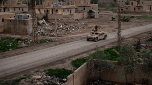 A Humvee drives in a village recently retaken from Islamic State militants by U.S.-backed Syrian Democratic Forces (SDF) near Baghouz, Syria, Sunday, Feb. 17, 2019. (AP Photo/Felipe Dana)
