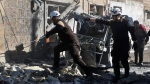 This photo released on Monday, Feb. 18, 2019 by the Syrian Civil Defense group known as the White Helmets, shows Syrian White Helmet civil defence workers in a street hit by a shell from Syrian forces, in the town of Maaret al-Numan, Idlib, north Syria. (Syrian Civil Defense White Helmets via AP)