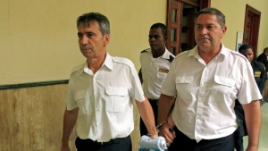 In this June 17, 2014 file photo, French pilots Bruno Odos, left, and Pascal Jean Fauret, who have been formally charged with drug trafficking, are escorted to a courtroom in Santo Domingo, Dominican Republic. (AP Photo/Ezequiel Abiu Lopez, File)