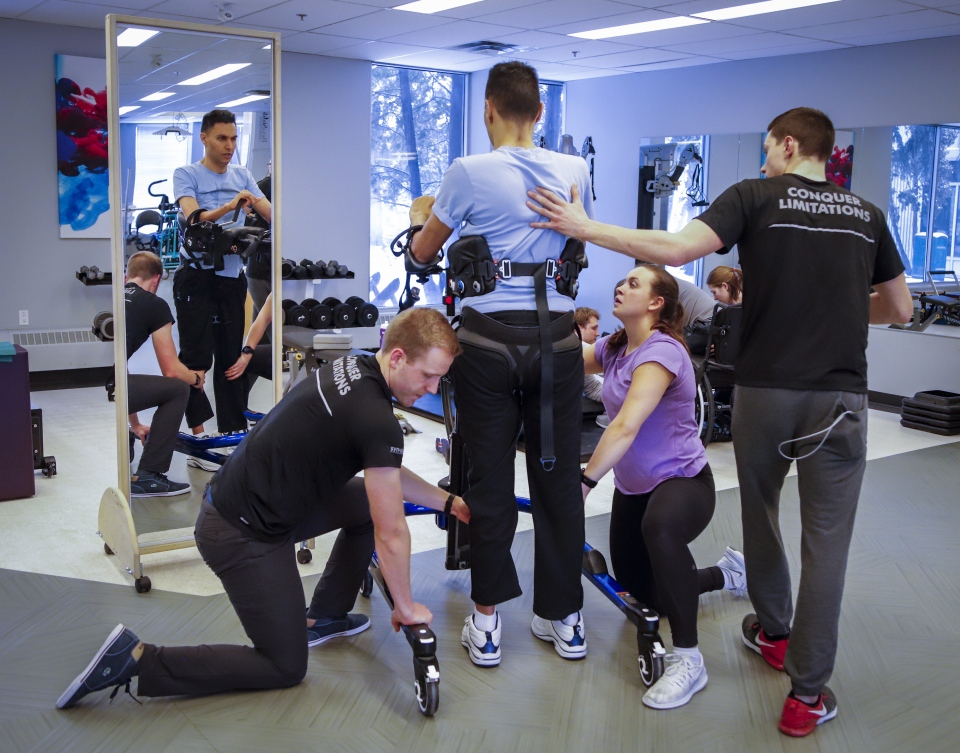 Dr. Richi Gill, in grey shirt, a Calgary doctor, takes part in physiotherapy in Calgary, Alta., Wednesday, Feb. 13, 2019. Dr. Richi Gill's life changed in an instant. The 38-year-old surgeon, who helped develop Calgary's bariatric surgery program, was involved in a freak accident on a boogie board during a family vacation in Hawaii one year ago. THE CANADIAN PRESS/Jeff McIntosh