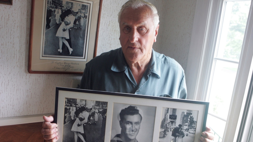 In this July 2, 2009, photo George Mendonsa poses for a photo in Middletown, R.I., holding a copy of the famous Alfred Eisenstadt photo of Mendonsa kissing a woman in a nurse's uniform in Times Square on Aug. 14, 1945, while celebrating the end of World War II, left. (Connie Grosch/Providence Journal via AP)