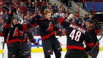 Carolina Hurricanes' Warren Foegele (13) and teammates celebrate at center ice after a win over the Edmonton Oilers, Friday, Feb. 15, 2019, in Raleigh, N.C. (AP Photo/Karl B DeBlaker)