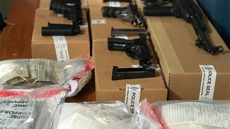 Toronto police seize drugs, guns in raids, arrest one man