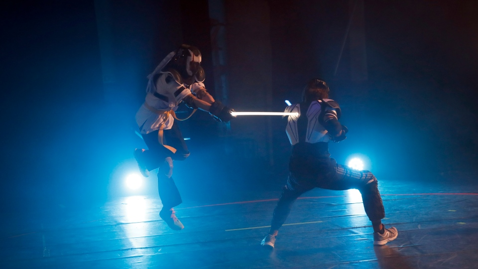In this Sunday, Feb. 10, 2019, photo, competitors battle during a national lightsaber tournament in Beaumont-sur-Oise, north of Paris. (AP Photo/Christophe Ena)