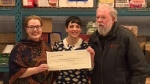 'Come From Away' cast member Steffi DiDomenicantonio (centre) presents a cheque to Eg Walters in Newfoundland, on Monday, Feb. 18, 2019.