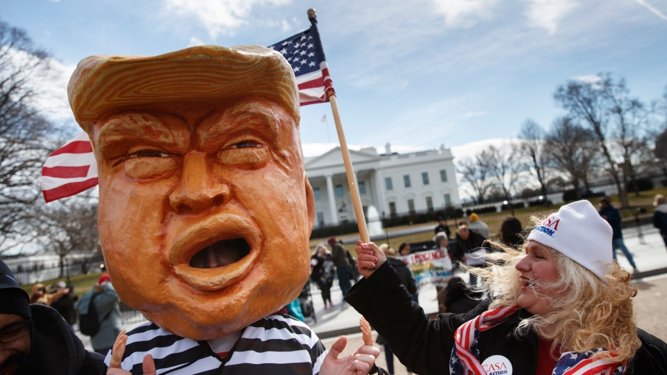 A person dressed to look like U.S. President Donald Trump in a prison uniform, and others gather Monday, Feb. 18, 2019, in front of the White House in Washington, to protest that Trump's declaration of a national emergence along the southern boarder. (AP Photo/Carolyn Kaster)