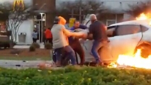This is the dramatic moment brave bystanders pulled a woman through the driver's window of a car engulfed in flames in Louisiana.(Storyful/Facebook)