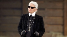 Chanel designer Karl Lagerfeld takes a bow at the end of his Metiers d'Art fashion show, Tuesday, Dec. 10, 2013, in Dallas. (AP Photo/Tony Gutierrez)