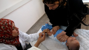 In this June 10, 2010 photo, a Palestinian woman helps a nurse to give her baby a vaccination, at the United Nations Relief and Works Agency (UNRWA) clinic, in Gaza City. (AP Photo/Khalil Hamra)