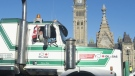 A passenger raises his arm as the convoy pulls in front of the Parliament buildings in Ottawa, Tuesday, February 19, 2019. THE CANADIAN PRESS/Adrian Wyld