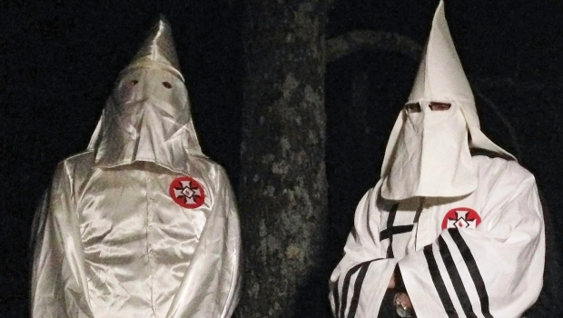 In this Friday, Dec. 2, 2016 photo, two masked Ku Klux Klansmen stand on a muddy dirt road during an interview near Pelham, N.C. (AP Photo/Jay Reeves)