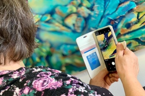 Robyn Rennie uses her smartphone to magnify her artwork in Barrie, Ont. on Tues., Feb. 19, 2019 (CTV News/Craig Momney)