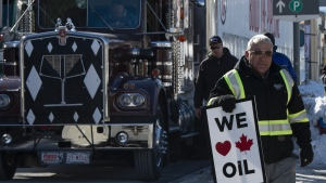 A pro-oil protester stands near convoy vehicles in front of Parliament Hill in Ottawa, Tuesday Feb. 19, 2019. THE CANADIAN PRESS/Adrian Wyld