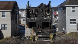 Firefighters investigate following a house fire in the Spryfield community in Halifax on Tuesday, February 19, 2019. THE CANADIAN PRESS/Darren Calabrese