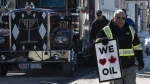 A pro-oil protester stands near convoy vehicles infront of Parliament Hill in Ottawa, Tuesday February 19, 2019. THE CANADIAN PRESS/Adrian Wyld