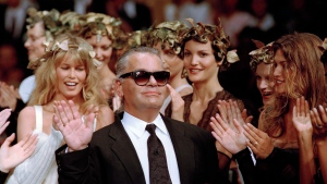 FILE - In this July 20, 1993 filer, German fashion designer Karl Lagerfeld acknowledges the applause of his models at the end of the show he designed for the French fashion house Chanel, for the 1993-94 Fall-Winter haute couture collection in Paris, July 20, 1993. At left background is German top model Claudia Schiffer. Chanel's iconic couturier, Karl Lagerfeld, whose accomplished designs as well as trademark white ponytail, high starched collars and dark enigmatic glasses dominated high fashion for the last 50 years, has died. He was around 85 years old. (AP Photo/Lionel Cironneau, File)