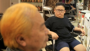 Le Phuc Hai, 66, left, and To Gia Huy, 9, sit after having Trump and Kim haircuts in Hanoi, Vietnam, on Tuesday, Feb.19, 2019. U.S. President Donald Trump and North Korean leader Kim Jong Un have become the latest style icons in Hanoi, a week before their second summit is to be held in the capital city of Vietnam.(AP Photo/Hau Dinh)