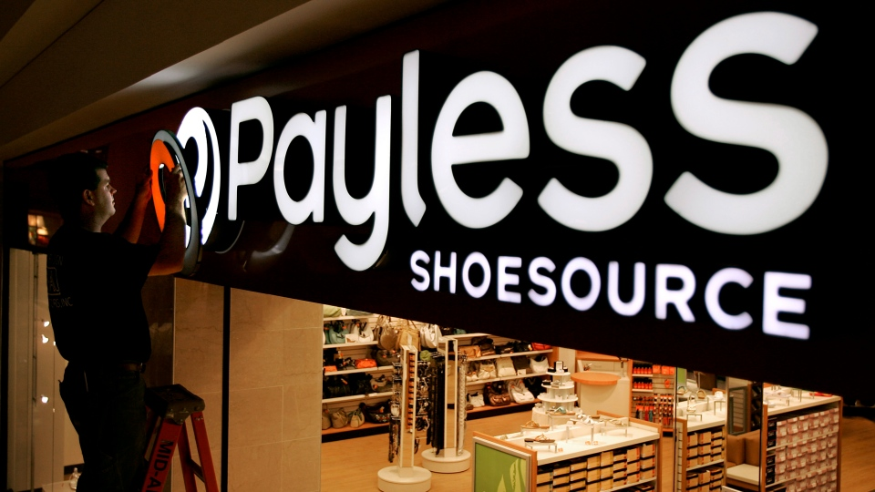 In this May 18, 2006, file photo a worker puts the finishing touches on a sign unveiling the company's new look at a Payless Shoesource store at a mall in Independence, Mo. (AP Photo/Charlie Riedel, File)